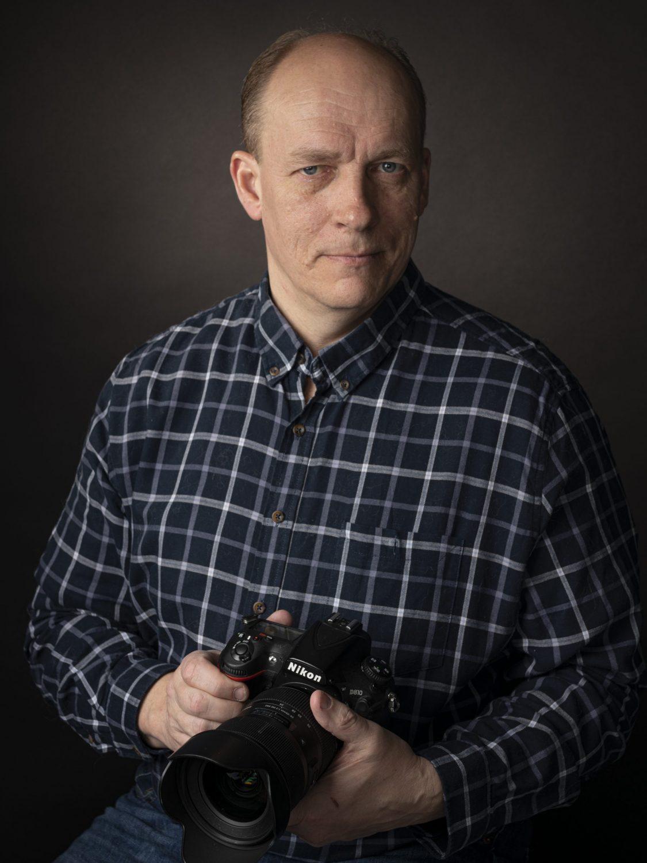 Valokuvaaja Jarmo Rantanen poseeraan kamera kädessään